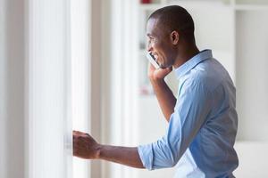 uomo d'affari americano africano utilizzando un telefono cellulare foto