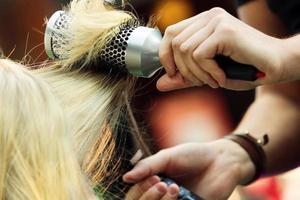 parrucchiere che pettina i capelli della ragazza foto