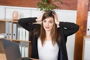 donna annoiata di affari del brunette che scrive sul suo computer portatile foto