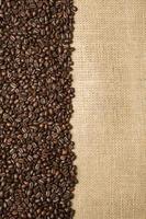 chicchi di caffè sullo sfondo di tessuti di iuta foto