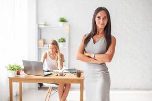 Ritratto di donna d'affari con le braccia incrociate e sorridente dentro foto