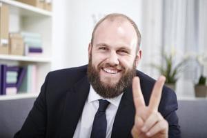 glücklicher geschäftsmann zeigt zwei finger in die kamera foto