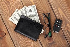 portafoglio, banconote da 100 dollari, occhiali e chiave elettronica dell'auto foto