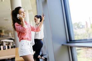 belle donne che usano il telefono e parlano durante la pausa foto