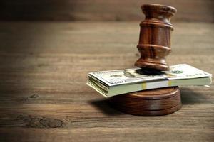 fascio di soldi, martelletto dei giudici e tavola armonica sul tavolo di legno