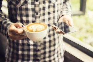 ragazza hipster con cappuccino e smartphone foto