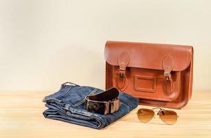 natura morta con borsa in pelle marrone, jeans e occhiali da sole foto