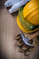 occhiali da costruzione martello da carpentiere piani di costruzione elmetto e guanti di sicurezza foto