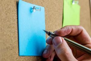 scrivendo su carta blu post-it foto