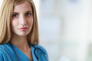 Ritratto di medico donna con cartella in corridoio dell'ospedale foto