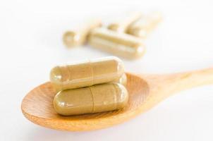 capsula di droga a base di erbe sul cucchiaio di legno foto