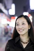 donna sorridente fuori di notte in città, ritratto