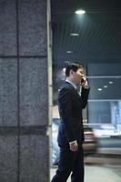 uomo d'affari che parla al telefono in un garage foto