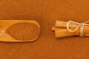 polvere di cannella, bastoncini e cucchiaio foto