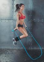 perdita sportiva di forma fisica di salto di sport della corda di salto di concetto della donna sportiva foto