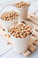 salute alimentare-soia, baccelli di soia nel secchio bianco su tavola di legno foto