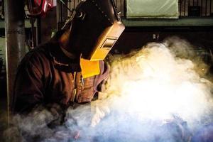 saldatura del saldatore nella nuvola di fumo foto