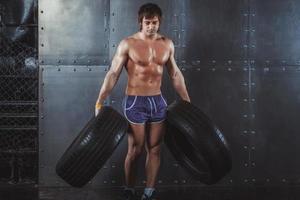 sportivo atleta palestra uomo che risolve esercitandosi con le gomme foto