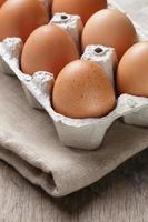 uova di gallina crude marroni in contenitore