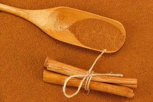 polvere di cannella, bastoncini e cucchiaio
