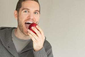 giovane uomo che mangia una mela rossa foto