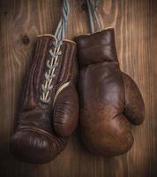 guantoni da boxe appesi sulla parete di legno foto