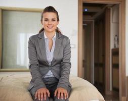 donna felice di affari che si siede sul letto nella camera di albergo foto