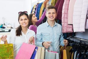 coppia portando borse in boutique foto