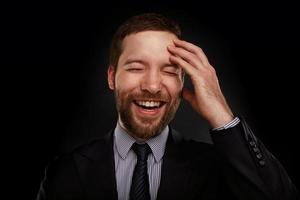 Ritratto di felice sorridente giovane imprenditore in una tuta foto