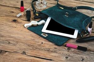 borsa da donna in pelle scamosciata con tablet computer, orologi e cosmetici da donna foto