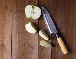 coltello da cucina e mela verde sullo sfondo di legno foto