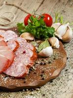 fette di prosciutto e salsicce affumicate su un tagliere foto