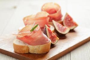 tartine con jamon e fichi su tavola di legno foto