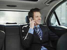 uomo d'affari utilizzando il telefono cellulare in auto foto