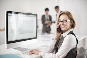 Ritratto di donna d'affari sorridente al telefono foto