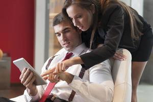 la donna di affari che esamina i colleghi maschi mette la spalla che indica alla compressa digitale foto