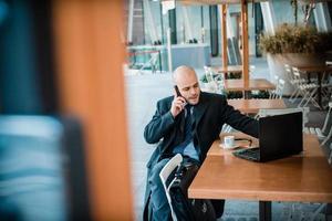 uomo d'affari in un bar al telefono e usando il portatile foto