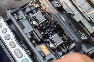 lavorando con giuntatrice a fusione in fibra ottica foto
