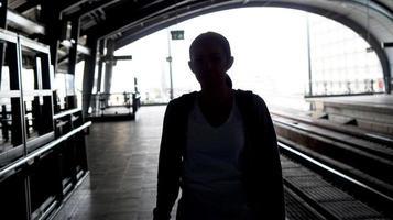 viaggiatore con zaino e sacco a pelo della ragazza turistica della siluetta che aspetta treno al foto