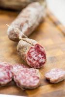 fette di salame italiano sul tagliere con coltello da cucina foto