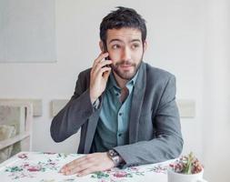 giovane uomo che indossa giacca seduto nel ristorante foto