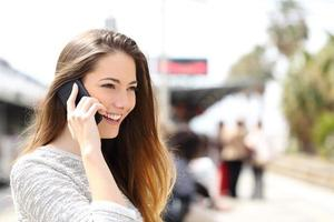 donna che parla al telefono in attesa in una stazione ferroviaria foto