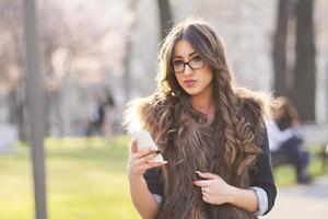 giovane donna con gli occhiali con il cellulare foto