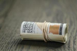 rotolo di cento banconote in dollari sul tavolo di legno foto