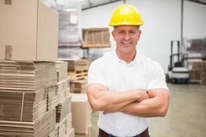 lavoratore che porta cappello duro in magazzino foto