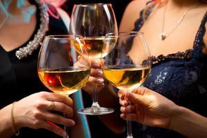 mani delle donne con bicchieri di vino in cristallo foto