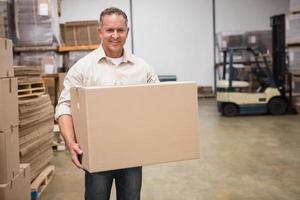 lavoratore sorridente che trasporta una scatola foto