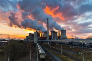 centrale elettrica a carbone con cielo al tramonto in fiamme foto
