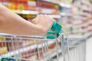 donna con carrello della spesa in un supermercato. foto