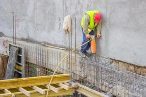 operaio costruttore usando un martello pneumatico foto